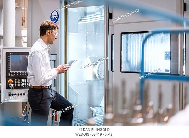 Businessman at machine in factory wearing safety goggles holding laptop