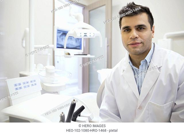 Portrait of confident dentist in office