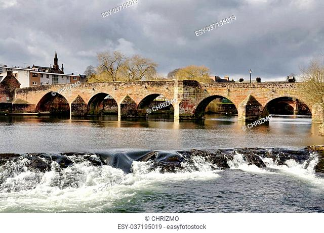Devorgilla Bridge, a 15th century crossing on the River Nith, with water flowing over the weir, on a winters day in Dumfries, Scotland