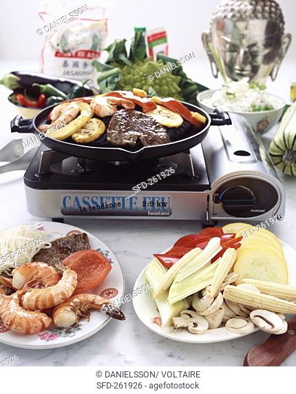Meat, shrimps and vegetables on table grill Asia