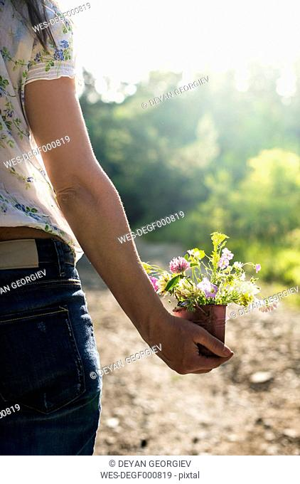 Woman holding small bucket with wildflowers in her hand