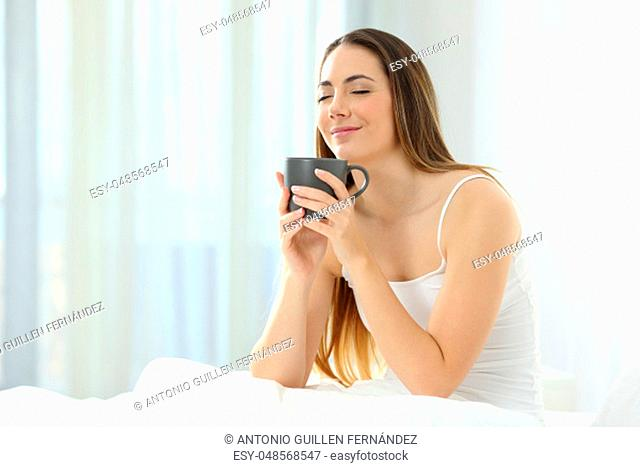 Relaxed woman waking up enjoying a cup of coffee on the bed at home in the morning
