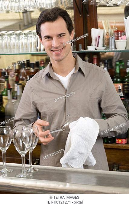 Male bartender drying wine glasses