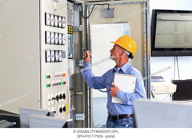 Electrical engineer inspecting power plant controls in central operations room of power plant