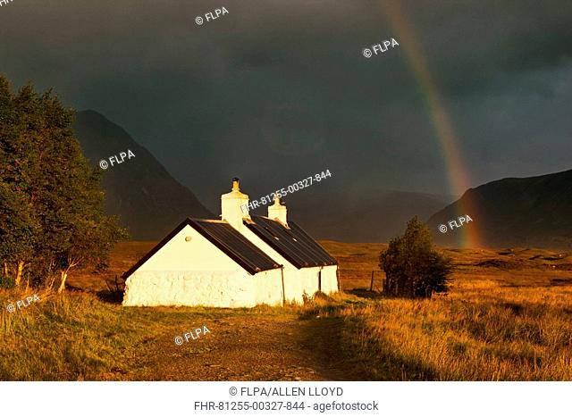 Blackrock cottage at dawn with rainbow and approaching storm, with Buachaille Etive Mor in background, Rannoch Moor, near Glencoe, Scotland