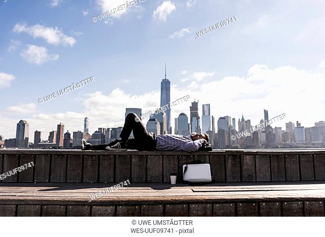 USA, man resting at New Jersey waterfront with view to Manhattan