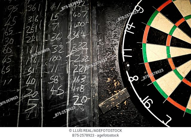 Close-up of a target of a darts game next to a blackboard with handwritten numbers with chalk. Pub in Yorkshire Dales, North Yorkshire, England, UK, Europe