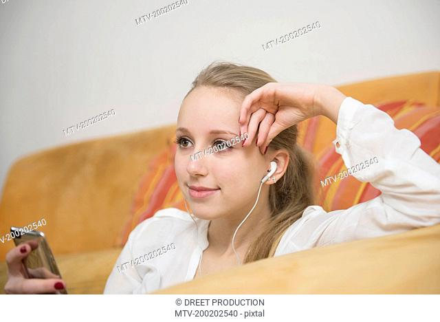 Teenage girl listening music with mp3, smiling