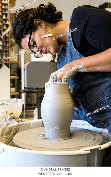 Woman working with a pottery wheel in her workshop