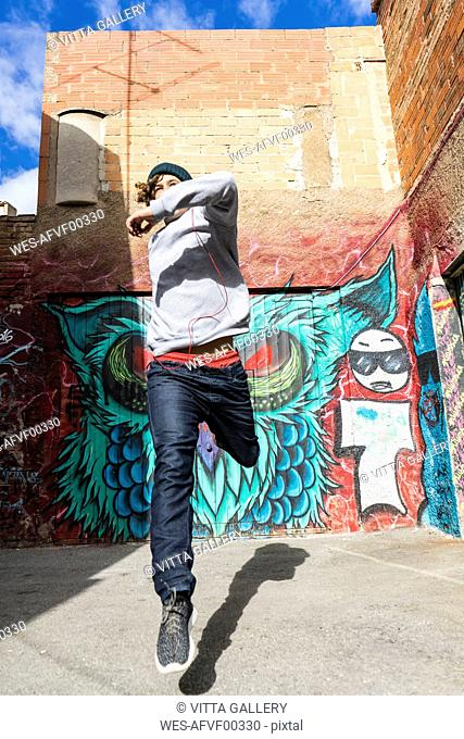 Young man with headphones jumping in the air in front of graffiti