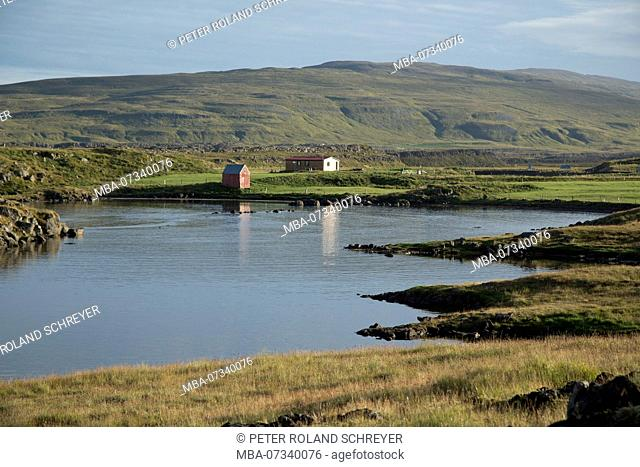 Iceland, Westfjords, lonely red house at the lake, mountains, autumn