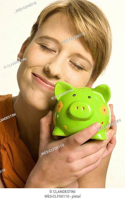 Young woman hugging piggy bank