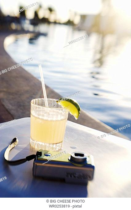 Margarita and camera on poolside table