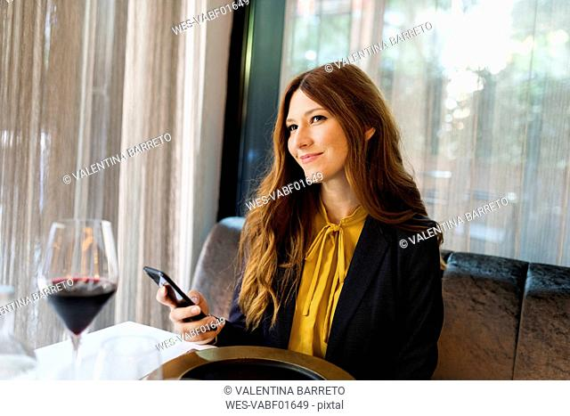 Smiling woman sitting at table in a restaurant holding cell phone