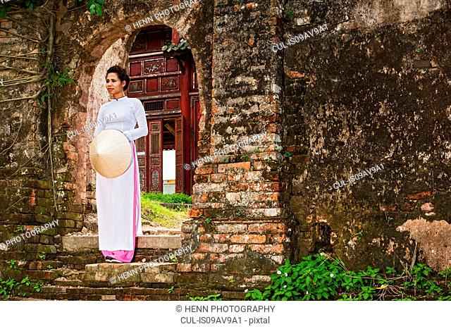 Mid adult woman wearing ao dai dress standing on step holding conical hat looking away, Hue, Vietnam