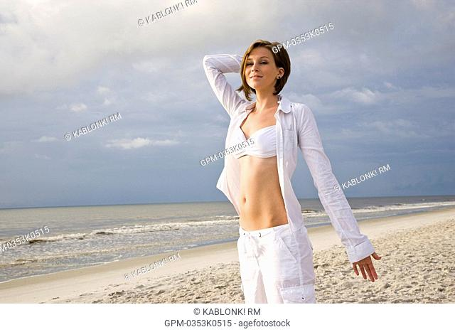 Portrait of young happy woman in white bikini top and pants standing on beach