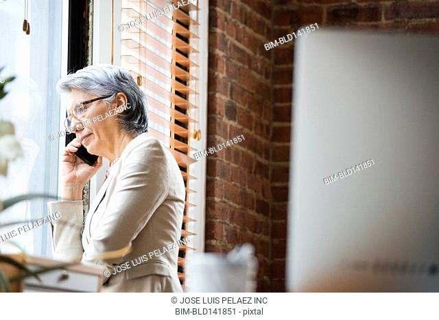 Hispanic businesswoman talking on cell phone in office