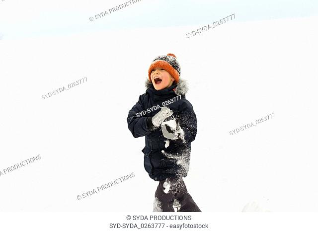 happy little boy playing with snow in winter