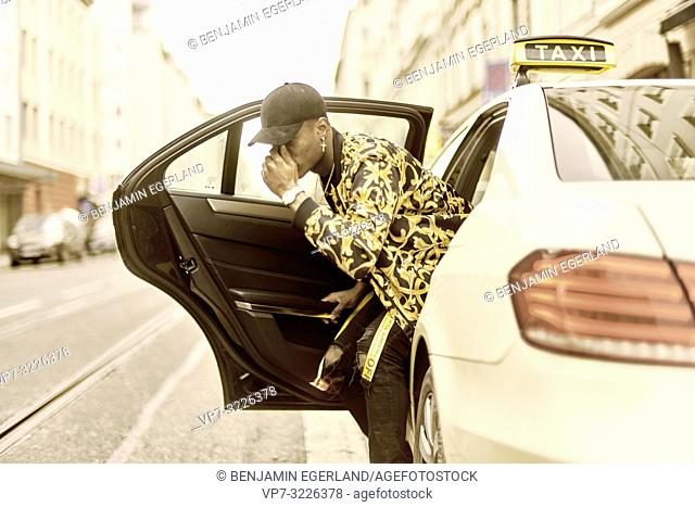 young famous stylish man getting out of taxi, exiting car, covering face with hand, at city street, wearing trendy fashion clothes, celebrity life, in Munich