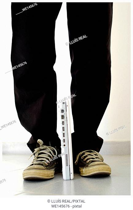 Closeup of legs of a man holding a laptop computer with his feet