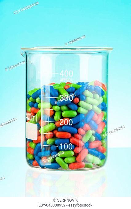 Laboratory glass container with green blue and red tablets and pills on blue