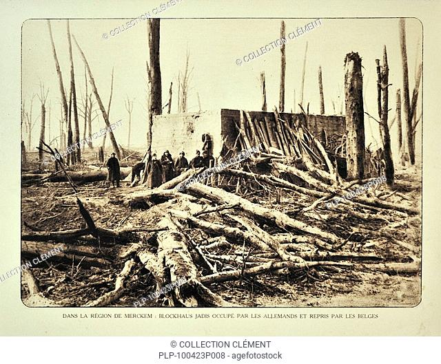 Soldiers standing next to bunker in bombarded forest at Merkem in Flanders during the First World War, Belgium