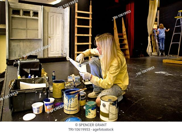 A high school student studies paint color samples while building the set of a play in her school's theatre. Stagecraft is an elective course at the school