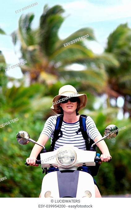 AITUTAKI - SEP 20:Tourist woman drives hired motorbike on Sep 20 2013.It's one of the must popular activity in the Island but Cook Islands Driver's License is...