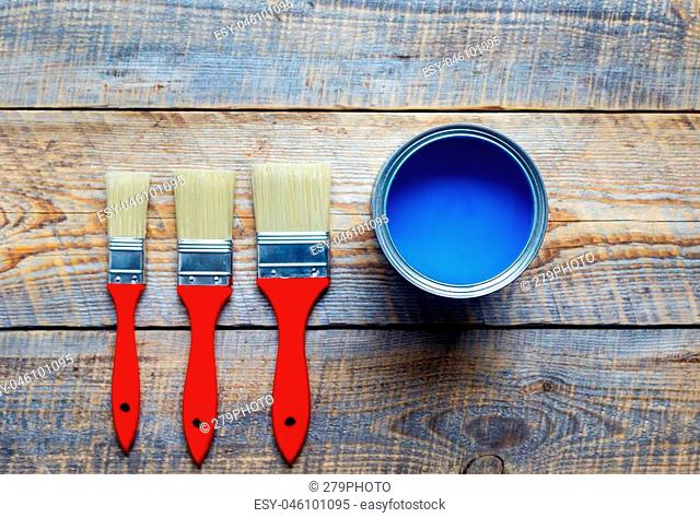 process of preparation for painting wooden floor at home with blue paint and the brushes top view