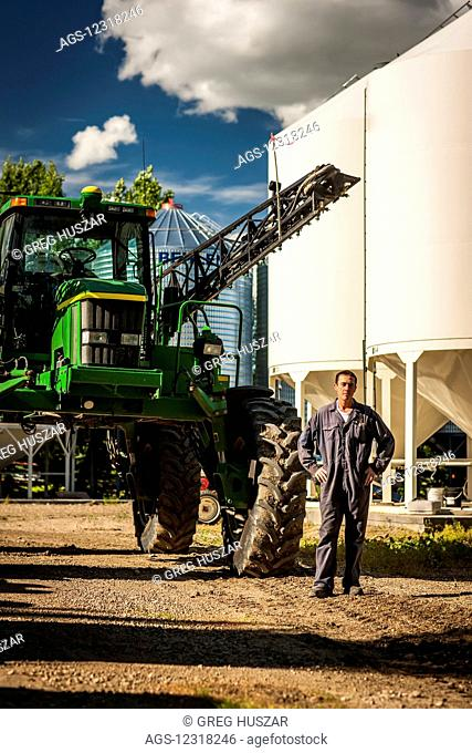 A young farmer stands posing beside a large tractor and grain storage bins on his farm; Herschel, Saskatchewan, Canada