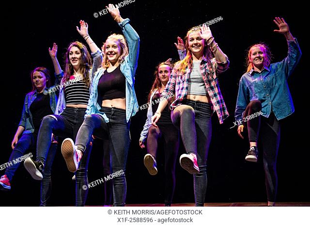 A group of teenage girls performing choreographed modern urban dance routines on stage at Aberystwyth Arets Centre Wales UK