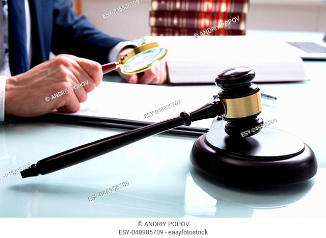 Male Justice Working On Legal Documents With Gavel In The Courtroom