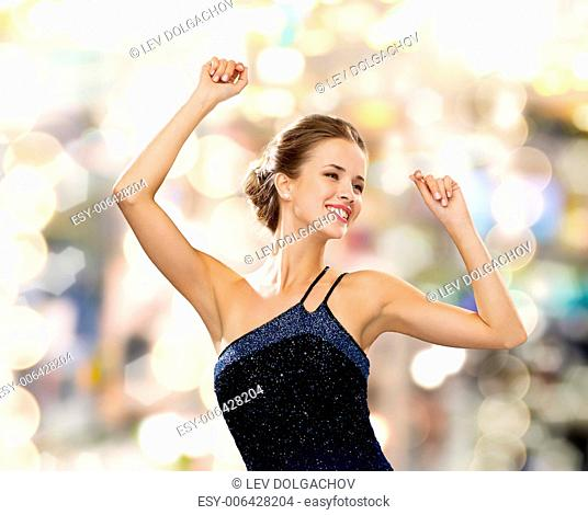 people, party, holidays and glamour concept - smiling woman dancing with raised hands over lights background