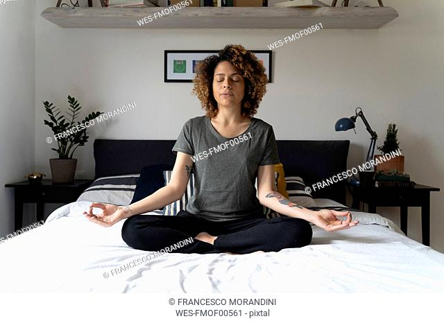 Woman practicing yoga, sitting on bed, meditating