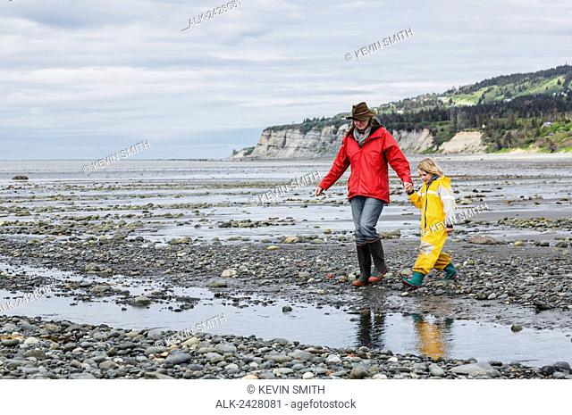 Mother and daughter walking on rocky section of Bishop's Beach at low tide, Kachemak Bay, Homer, Southcentral Alaska