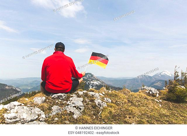 male hiker with red sweater is holding a german flag in the mountains in spring