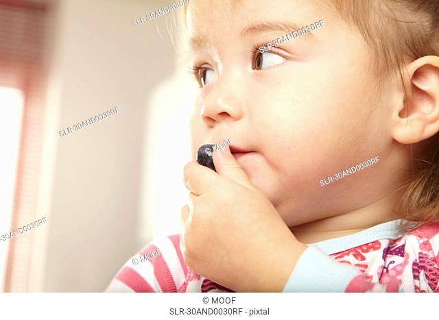 Young girl eating a blueberry