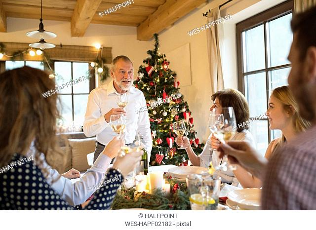 Senior man holding a speech with family at Christmas dinner