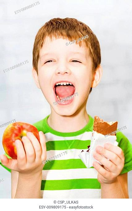 Child chooses chocolate or apple on a light background in the st