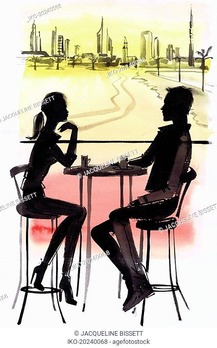 Young couple in cafe silhouetted against Dubai cityscape