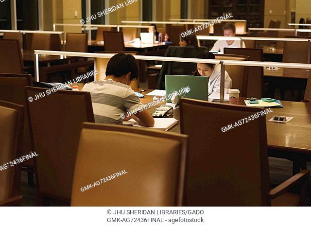 College students seated at study tables work from notebooks and laptops during the late hours of the night, the only light in the dim room coming from lamps on...
