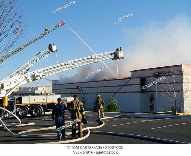 Fire trucks pour huge streams of water on a Michaels Store in Bowie, Maryland during a 3 alarm fire