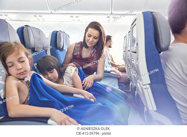Mother putting blanket on sleeping daughter on airplane