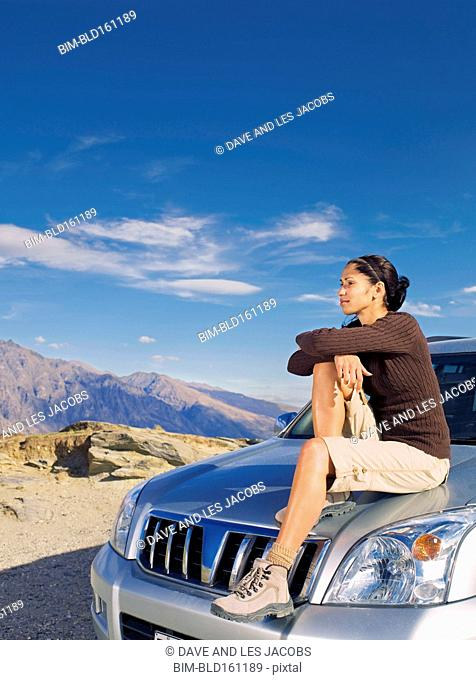 Hispanic woman sitting on car on remote road