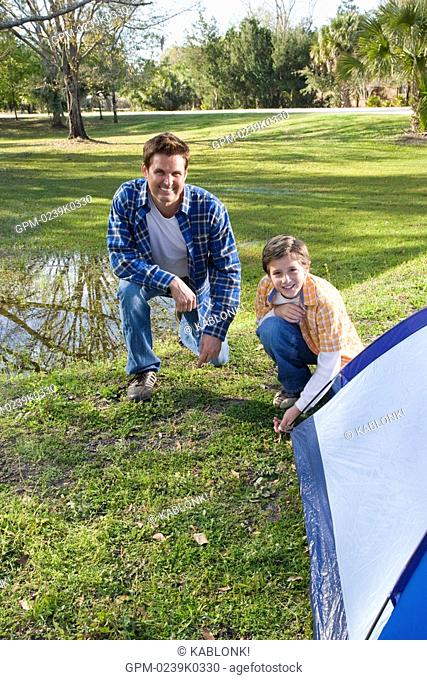 Portrait of son and father pitching tent in park