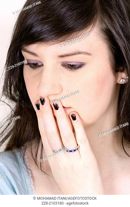 Woman hand covering mouth looking away