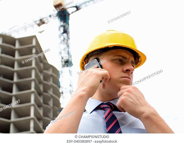 engineer in a helmet with a smartphone