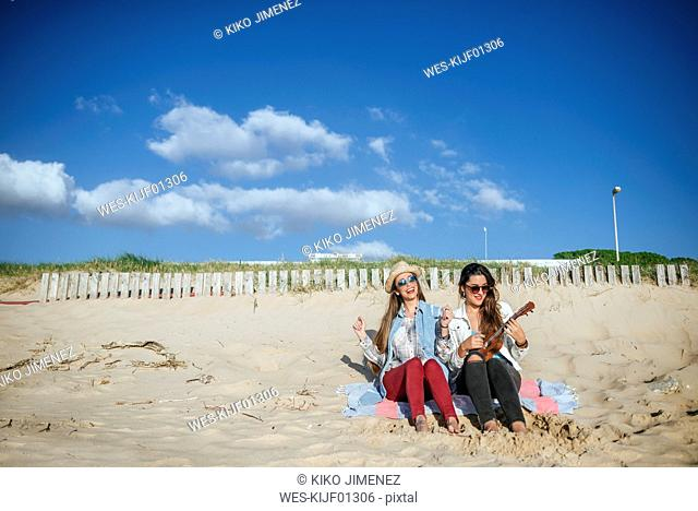 Two young women with ukulele sitting on blanket on the beach