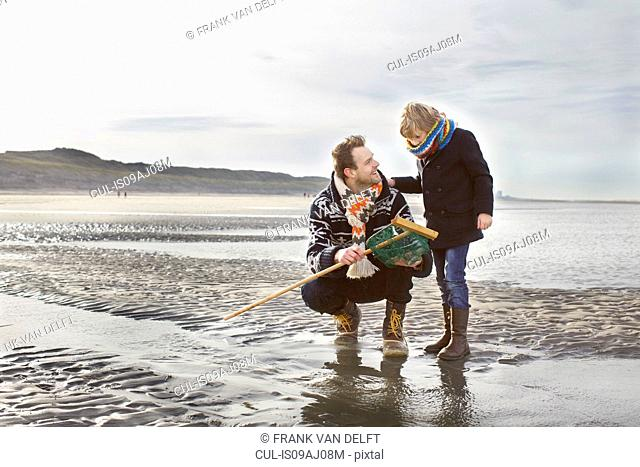 Mid adult man and son with fishing net on beach, Bloemendaal aan Zee, Netherlands