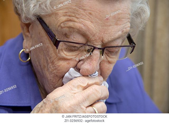 old woman reading book and whiping nose
